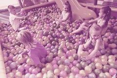 使用与多彩多姿的塑料球的孩子 免版税库存照片