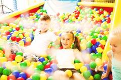 使用与多彩多姿的塑料球的孩子 免版税库存图片