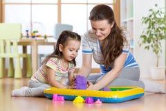 使用与大厦的儿童女孩和母亲在家戏弄沙子 免版税库存图片