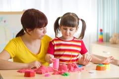使用与大厦的儿童女孩和母亲在家戏弄沙子 库存图片