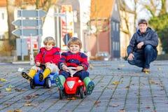 使用与大老玩具汽车的两个愉快的兄弟姐妹男孩和父亲, 免版税库存图片