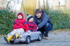 使用与大老玩具汽车的两个愉快的兄弟姐妹男孩和父亲, 免版税库存照片