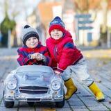 使用与大老玩具汽车的两个愉快的兄弟姐妹男孩,户外 免版税图库摄影