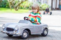 使用与大老玩具汽车的两个愉快的兄弟姐妹男孩 免版税库存照片