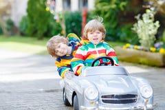 使用与大老玩具汽车的两个愉快的兄弟姐妹男孩 免版税库存图片