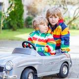 使用与大老玩具汽车的两个愉快的兄弟姐妹男孩 图库摄影