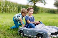 使用与大老玩具汽车的两个愉快的孩子在夏天从事园艺,室外 库存图片