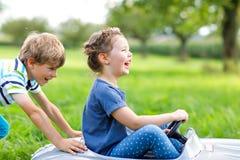 使用与大老玩具汽车的两个愉快的孩子在夏天从事园艺,室外 免版税库存图片