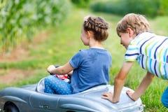 使用与大老玩具汽车的两个愉快的孩子在夏天从事园艺,室外 免版税图库摄影