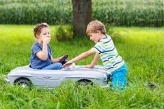 使用与大老玩具汽车的两个愉快的孩子在夏天从事园艺,室外 库存照片