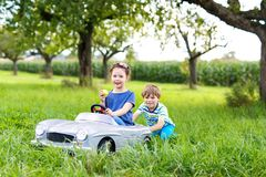 使用与大老玩具汽车的两个愉快的孩子在夏天从事园艺,室外 免版税库存照片