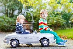 使用与大老玩具汽车的两愉快的孪生在夏天从事园艺, o 免版税库存照片