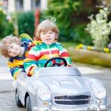 使用与大老玩具的两个愉快的兄弟姐妹男孩 免版税库存照片