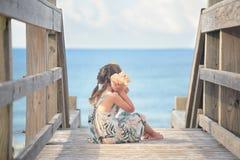 使用与大贝壳的小女孩在海洋附近 免版税库存照片
