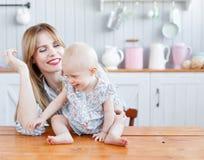 使用与她的一个现代厨房设置的小女儿的年轻母亲 那么逗人喜爱的家庭 有妈妈的滑稽的女孩厨房的 库存照片