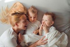 使用与她的两个儿子的年轻白肤金发的母亲在床上早晨 免版税图库摄影