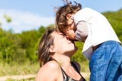使用与她的儿童女孩的愉快的母亲户外 免版税库存图片