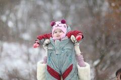 使用与她的冬景花园的婴孩的母亲 免版税库存照片