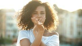 使用与她的卷发和执行在都市背景的一名年轻可爱的妇女性感的跳舞-明亮的日落 影视素材