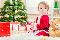 使用与她的圣诞节的圣诞老人衣服的小女孩戏弄 图库摄影