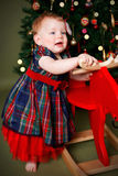 使用与她的圣诞节礼物的俏丽的婴孩 免版税库存照片
