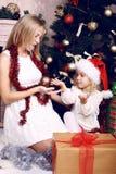 使用与她的在圣诞树旁边的母亲的圣诞老人的帽子的逗人喜爱的小女孩 库存图片