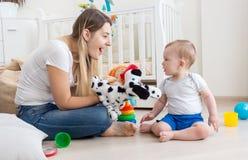 使用与她的在地板上的小儿子的年轻微笑的妇女在卧室 免版税库存图片