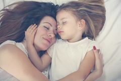 使用与她的在床上的小女儿的年轻母亲 享受toge 图库摄影