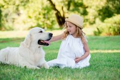 使用与她的大白色牧羊犬的小逗人喜爱的小孩女孩 选择聚焦 免版税库存图片