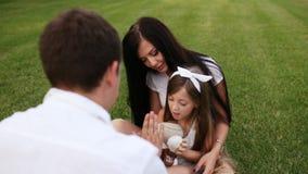 使用与她的女儿的愉快的家庭在城市公园 股票视频