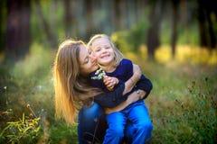 使用与她的女儿的母亲在平衡的公园,拥抱和微笑 免版税库存照片