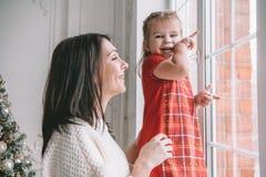 使用与她的女婴的爱的母亲看窗口 免版税库存图片