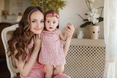 使用与她的女婴的愉快的年轻可爱的母亲画象在内部的窗口附近在haome。在母亲的桃红色礼服和 库存照片