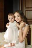 使用与她的女婴的愉快的年轻可爱的母亲画象在内部的窗口附近在haome。在母亲的桃红色礼服和 免版税库存图片