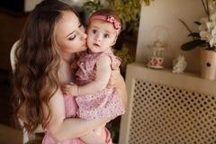 使用与她的女婴的愉快的年轻可爱的母亲画象在内部的窗口附近在haome。在母亲的桃红色礼服和 库存图片