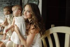 使用与她的女婴的愉快的年轻可爱的母亲画象在内部的窗口附近在haome。在母亲的桃红色礼服和 图库摄影