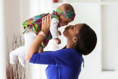 使用与她的女婴的年轻非裔美国人的母亲 库存照片