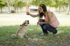 使用与她的宠物的逗人喜爱的狗所有者 库存图片