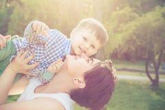 使用与她的小孩儿子的愉快的母亲在公园 库存照片