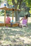 使用与她的小孩儿子的年轻母亲坐在沙盒 库存照片