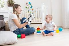 使用与她的小孩男孩的年轻微笑的妇女佩带的布袋木偶玩具 免版税库存照片
