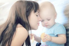 使用与她的漂亮的孩子的美丽的母亲,孩子吃曲奇饼和笑 免版税库存图片