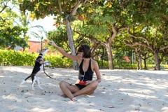 使用与她的爱犬小猎犬的年轻可爱的女孩在海滩热带海岛巴厘岛,印度尼西亚 愉快的时候 免版税库存照片