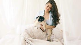 使用与她的狗的睡衣的可爱的妇女在床上 录影镜头 白天 股票录像