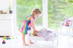 使用与她的玩具熊的愉快的卷曲小孩女孩 图库摄影
