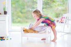 使用与她的玩具熊的逗人喜爱的卷曲小孩女孩 免版税库存照片