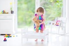 使用与她的玩具熊的逗人喜爱的卷曲小孩女孩 库存图片