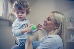 使用与她的男婴的年轻微笑的母亲 库存图片