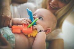 使用与她的男婴的年轻愉快的母亲 免版税库存图片