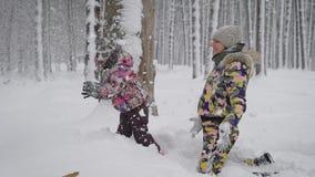 使用与她的雪的年轻母亲的小女孩户外在公园 愉快的孩子享受冬天 美妙地 股票视频